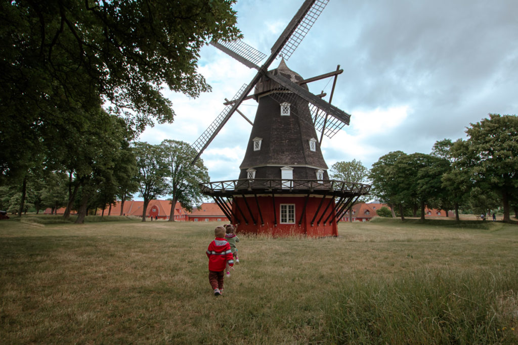 Twin toddlers run towards a historic windmill in Copenhagen