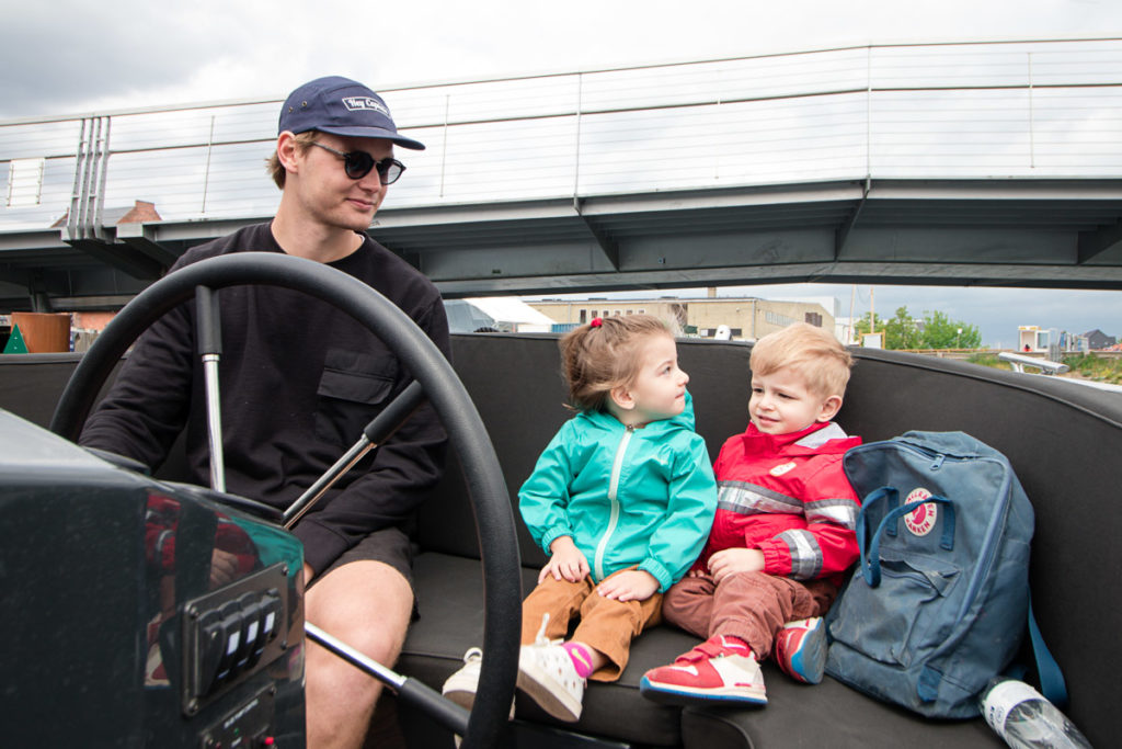 Twin toddlers sit next to captain of the boat tour in Copenhagen