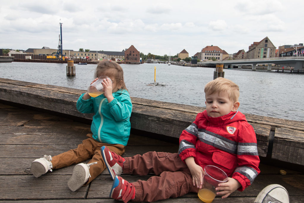 Twin toddlers drink apple juice in front of the royal playhouse in Copenhagen.