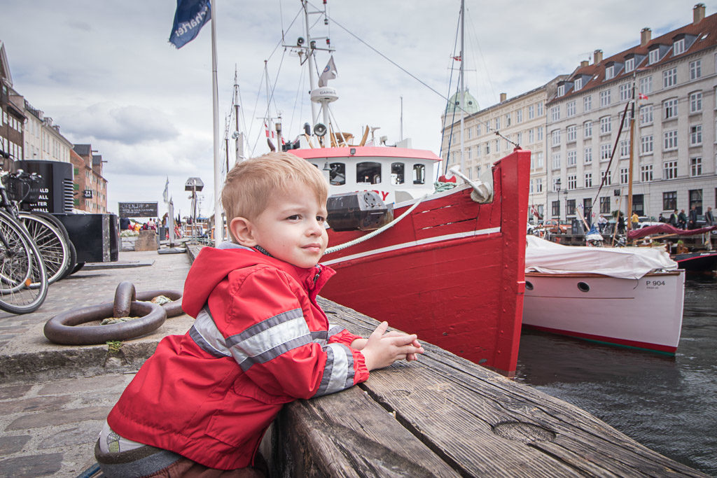 Toddler watches boats on the canal in Copenhagen