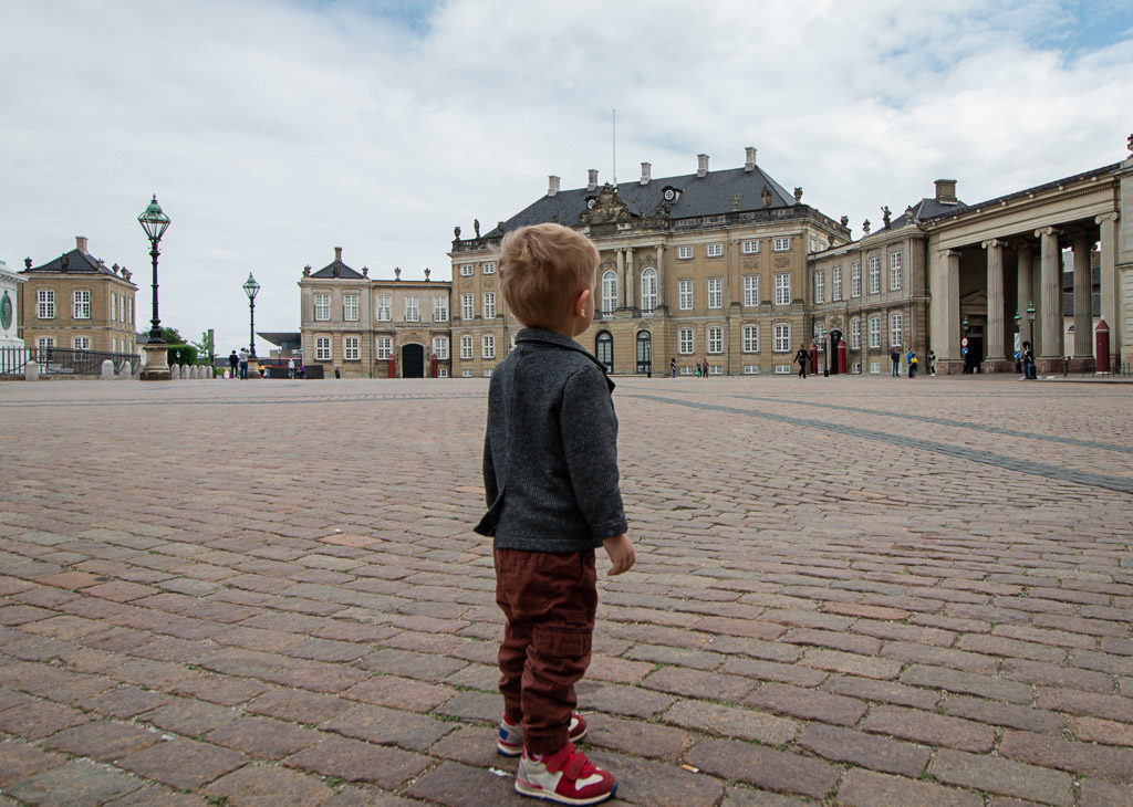 Toddler stands on palace grounds in Copenhagen Denmark