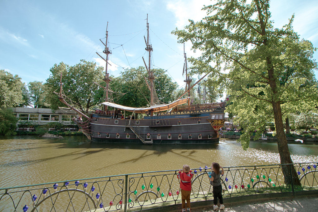 Twin todfdlers look at a pirate ship docked at Tivoli - amusement park copenhagen.