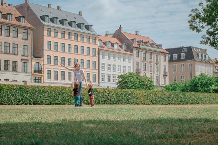 Mother teaches kids to play with sticks on a warm summer day in Copenhagen