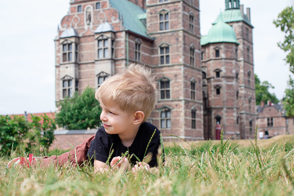Toddler lounges on the grass in front of a castle