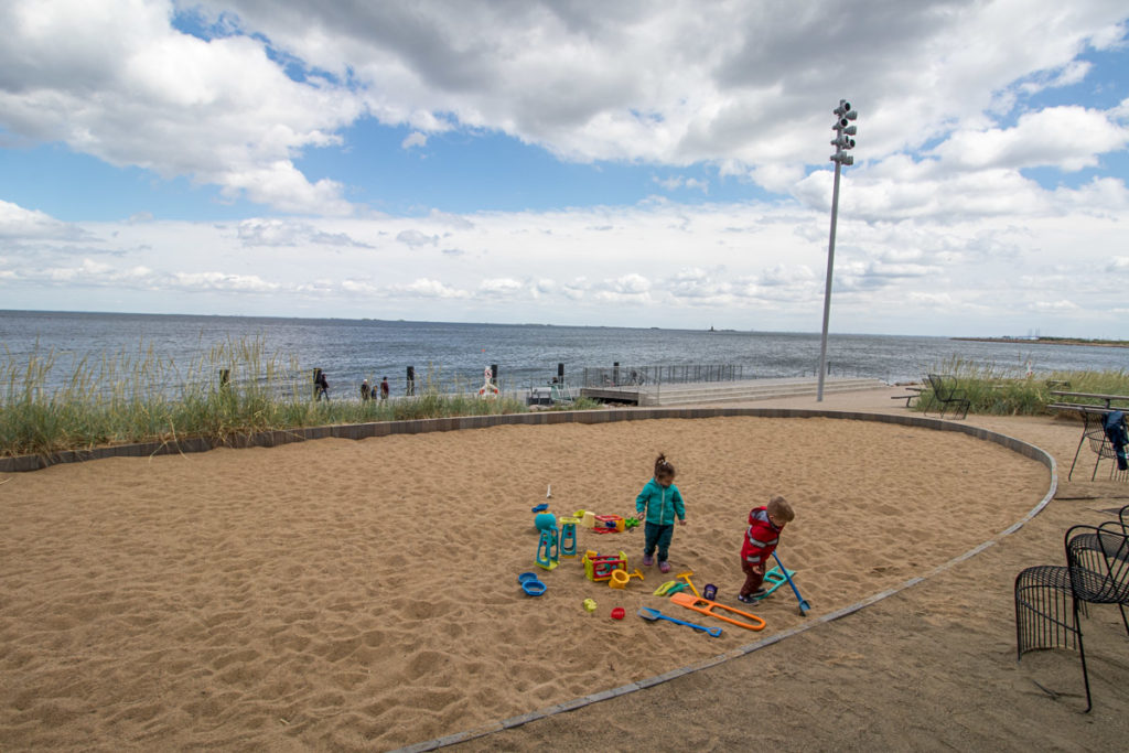 Toddlers play in massive sandbox outside of the aquarium in Copenhagen