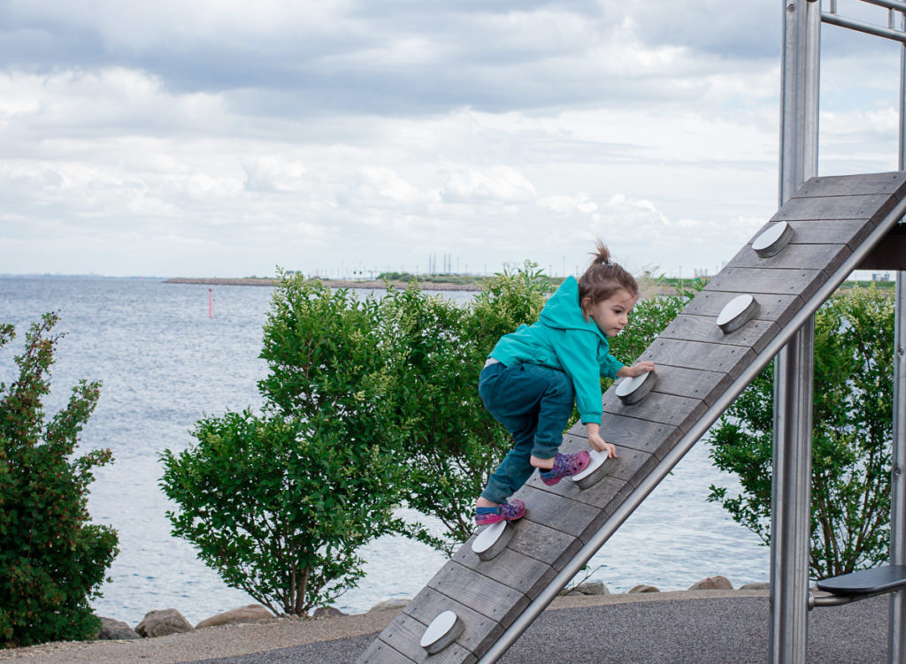 Toddler climbs slanted rock wall at a playground in Copenhagen