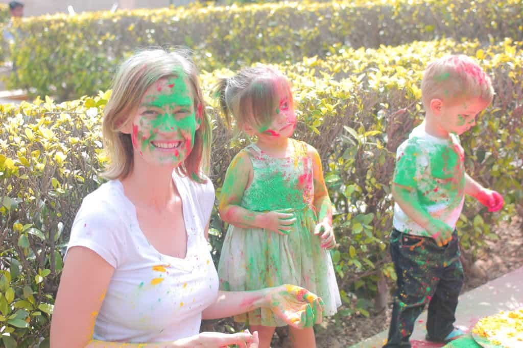 Mother and twin toddlers are covered in color on Holi.
