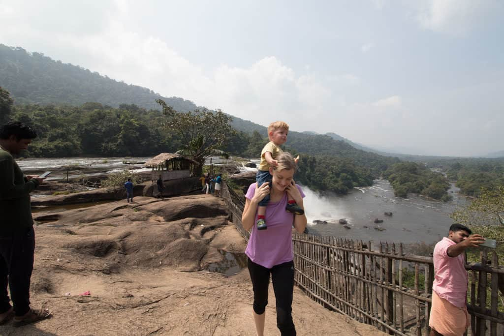 Mther walks with toddler on her shoulders - in the background a large waterfall is seen