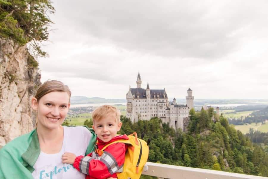 MOther and son pose in front of the fairy tale castle germany