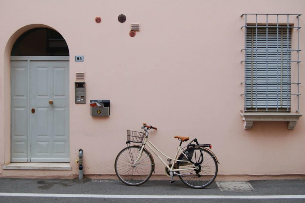 Bike leaned up a light pink wall