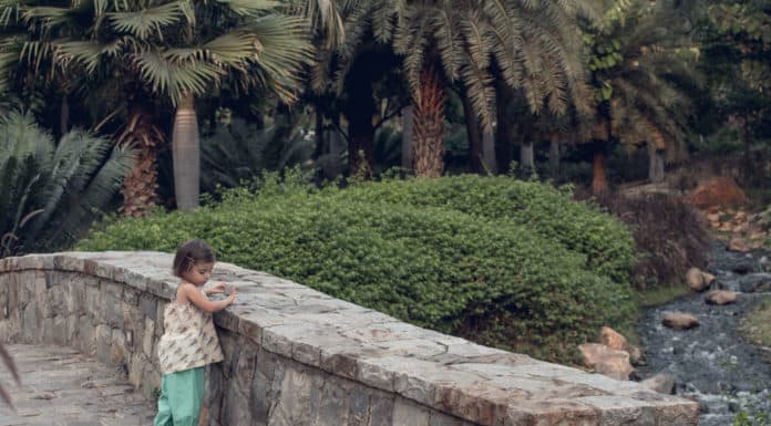Toddler looks over edge of a rock wall to see the stream in India