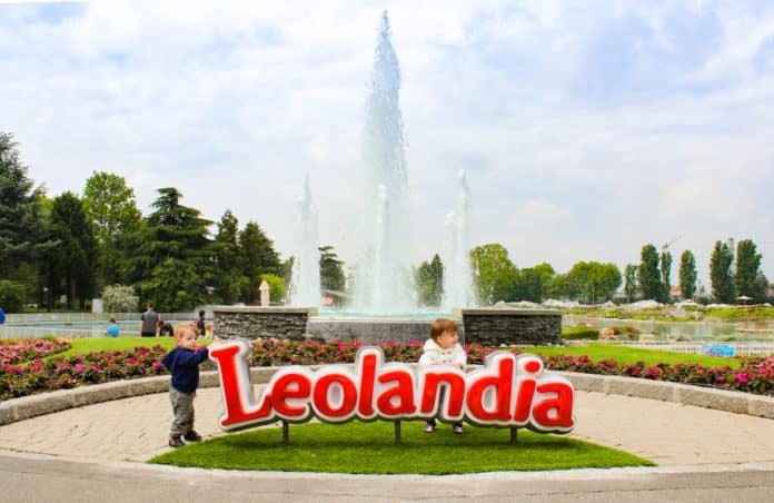 Two toddler stands next to Leolandia sign in Italy