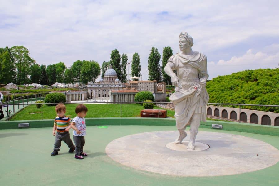 Toddler walks around life sized statue in minitalia