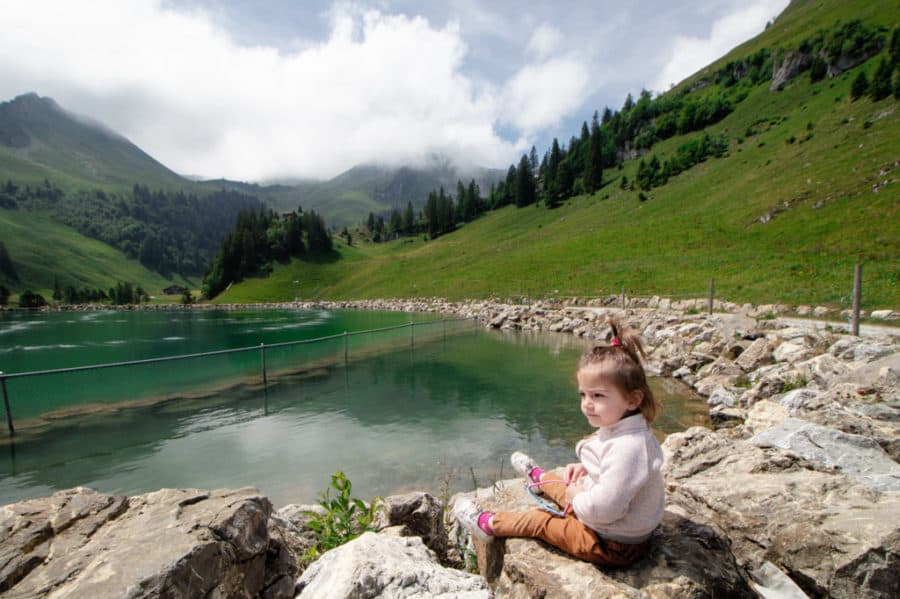 Toddler sits on rock and looks at beautiful lake.