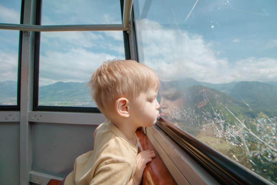 Boy looks out gondola window on the way up to the stoos