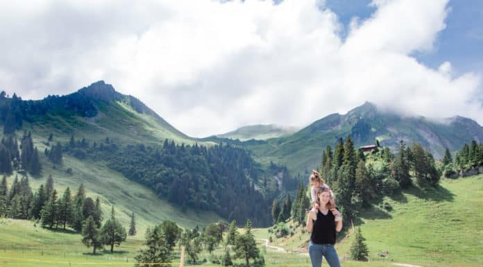 Mother stands in the Swiss alps with toddler on her shoulders. Stoos Switzerland