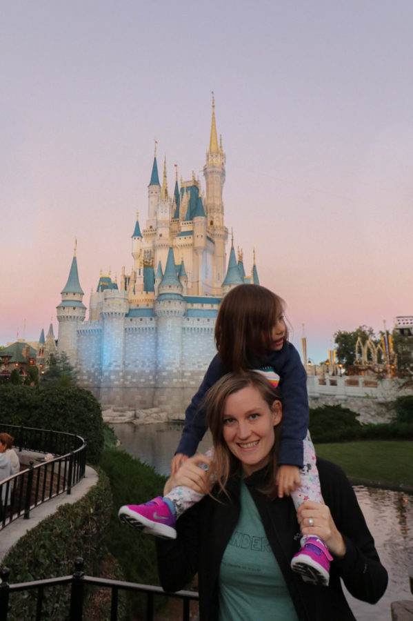 Toddler sits on mothers shoulders at Walt Disney World
