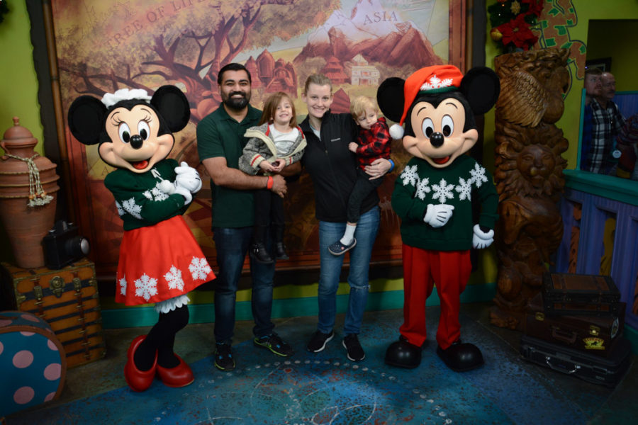 Parents and toddlers pose with Minney and Mickey mouse.