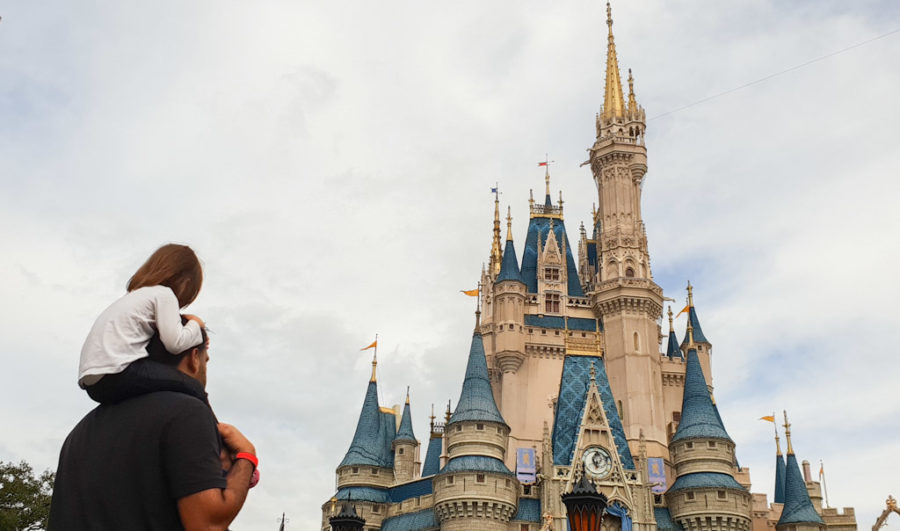 Girl sits on fathers shoulders with a view of the Walt Disney castle.