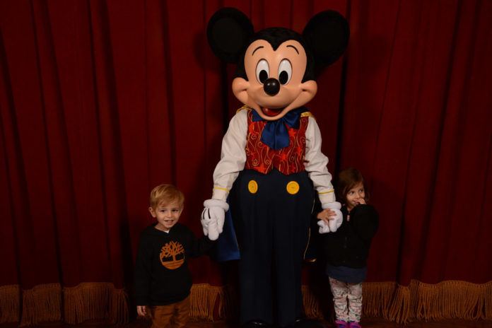 Two toddlers pose with Mickey Mouse in Walt Disney World. Taken by a Disney Photographer.