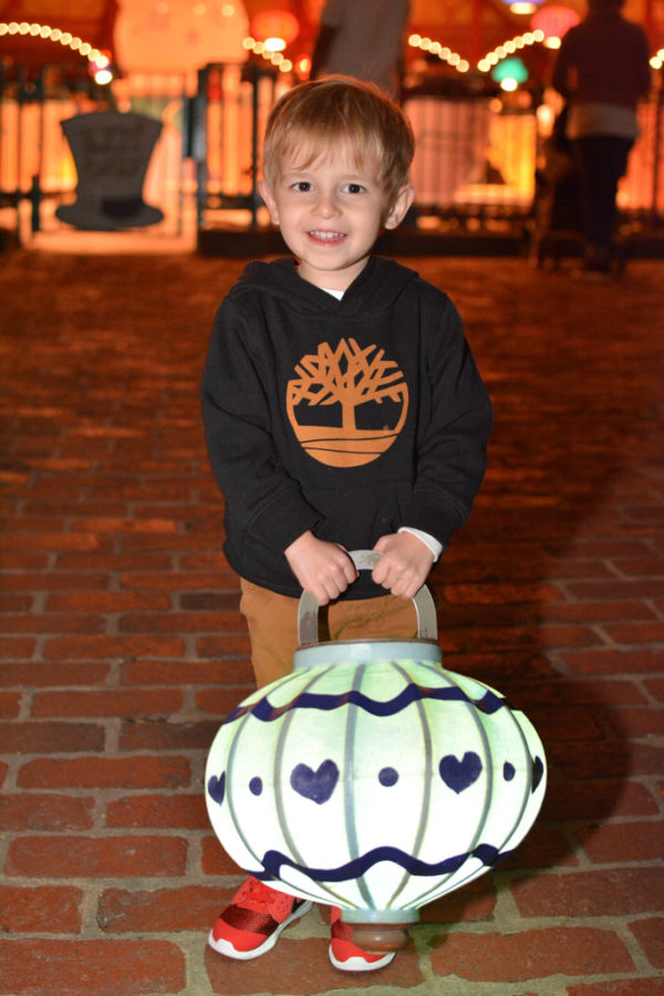Toddler boy poses with a giant lamp in Walt Disney World