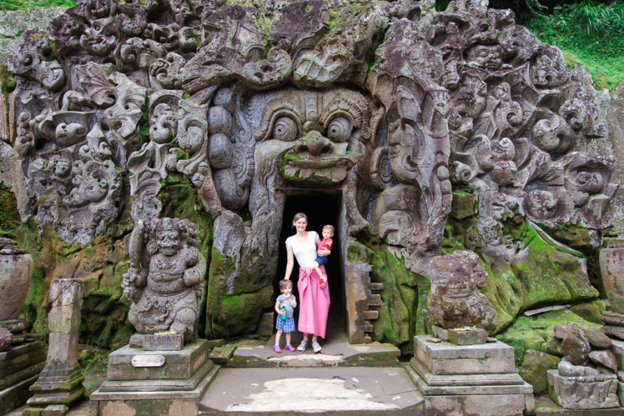 Mother stands in doorway of the elephant cave in Bali.