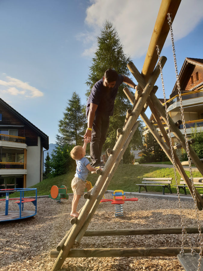 Father helps his son climb on a play structure at a very family friendly resort in Switzerland