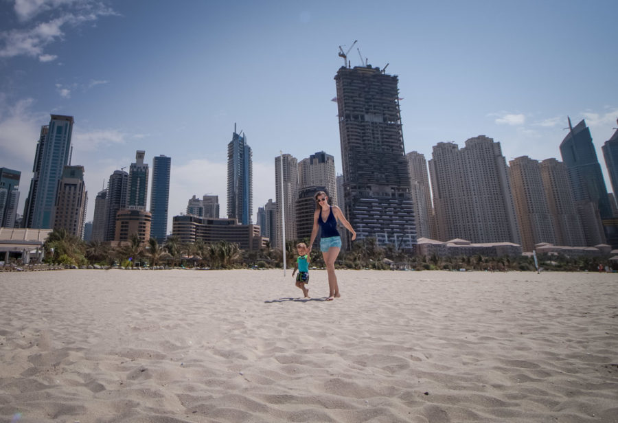 Mother and son walk along a beach in Dubai