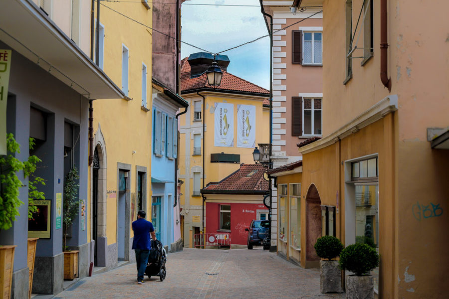 Man pushes a stroller down a cobblestone street in Locarno