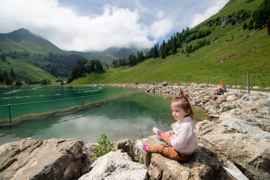 Toddler sits on a rock in the swiss alps