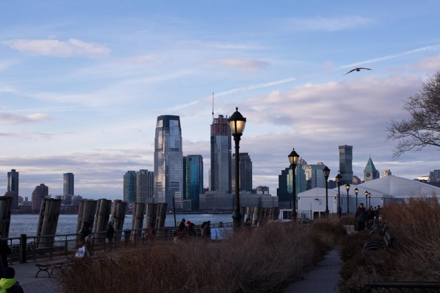 streetlights are on in Battery Park just after sunset.