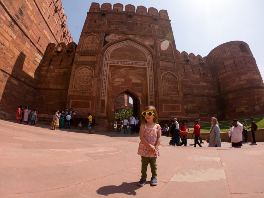 Travelling toddler stands at the entrance of the Agra Fort.