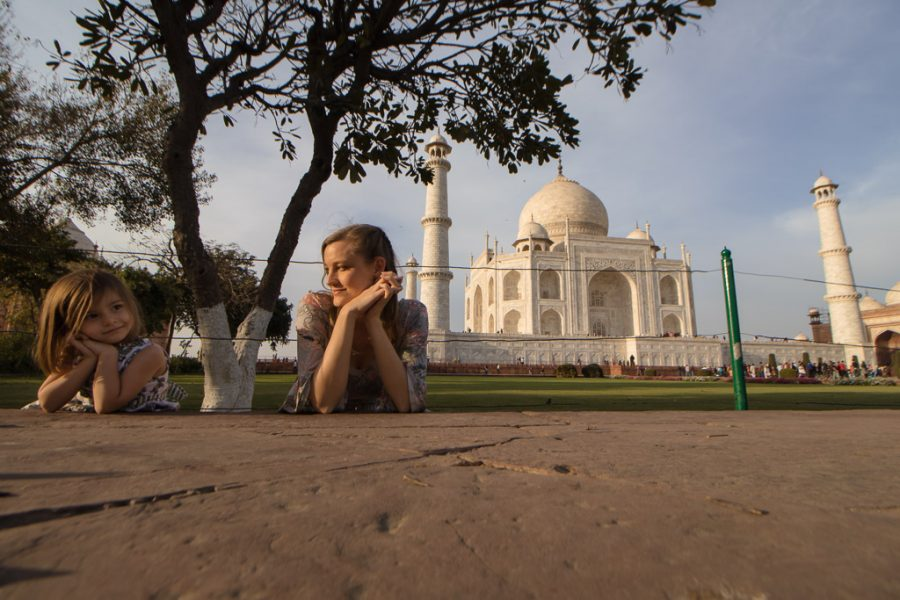 Mother and daughter tourists pose in front of the taj mahal on a weekend.