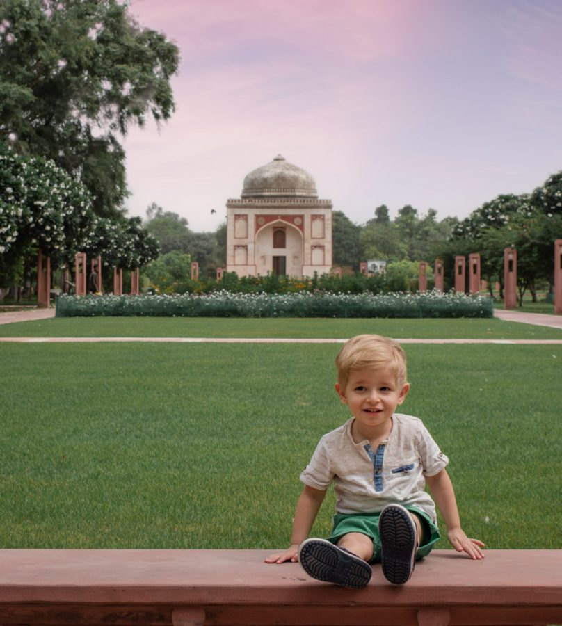 Toddler sits on a bench in front of a monument in August in New Delhi