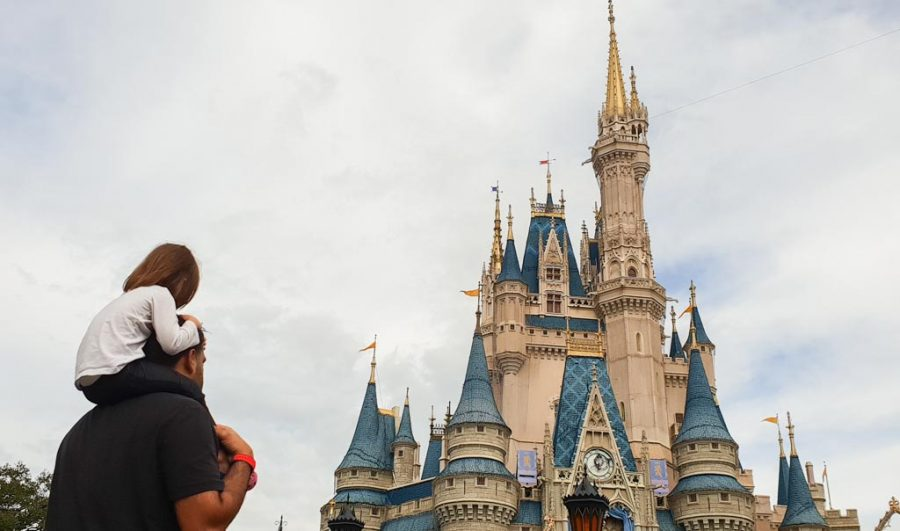 Toddler girl stares at the Disney Castle while sitting on her fathers shoulders