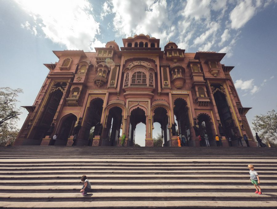 Toddlers play on the steps of a large gate in Jaipur, India