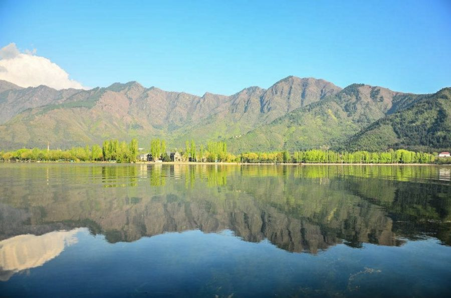 Lake in Kashmir is shown with a reflection of the mountains on the water