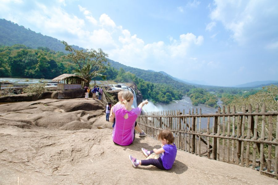 Mother and toddlers sit at a lookout over a large waterfall in Kerala