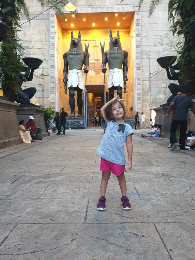 Toddler poses in front of the mummy roller coaster in USS.
