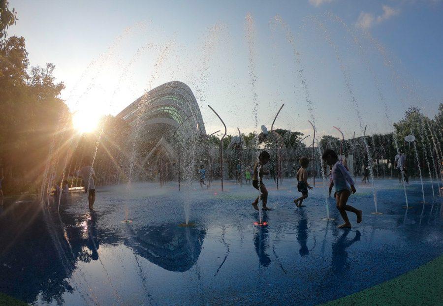 Children run around the Splash Pad in Singapore at Sunset.
