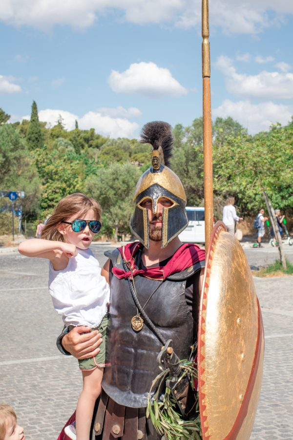 Small girl poses with a Gladiator at the base of the Acropolis when visiting Athens with kids