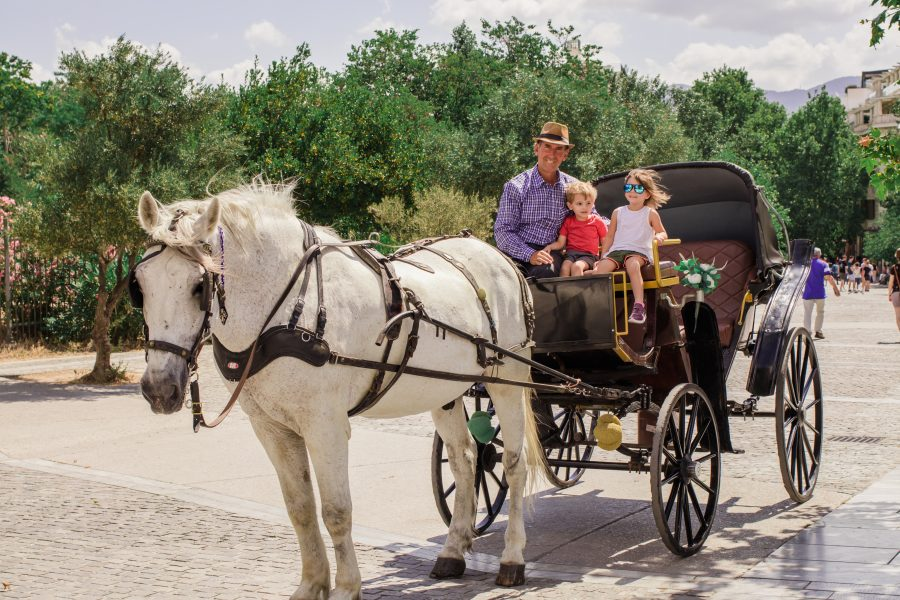 Two children pose on a horse drawn carriage at the base of the Acropolis.