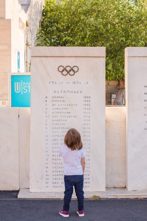 Small girl trys to read the Olympic sign in Athens
