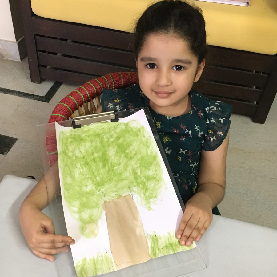 Preschooler holds up her tree painting using natural materials in her STEM activity