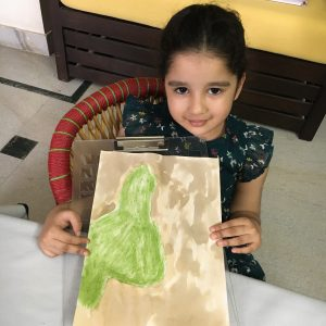 Preschooler holds up a painting.