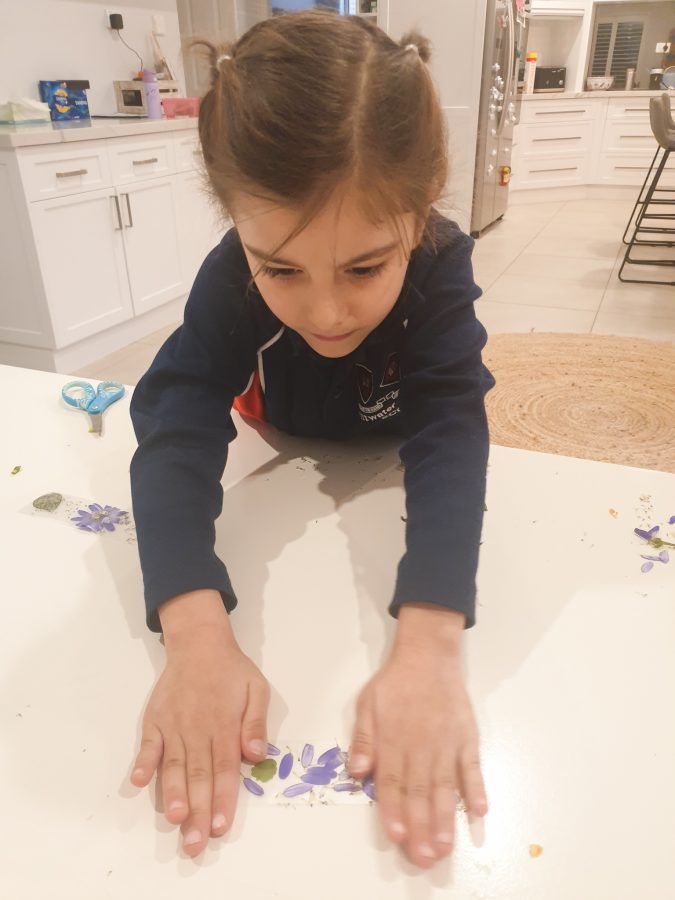Child seals her pressed flower bookmark