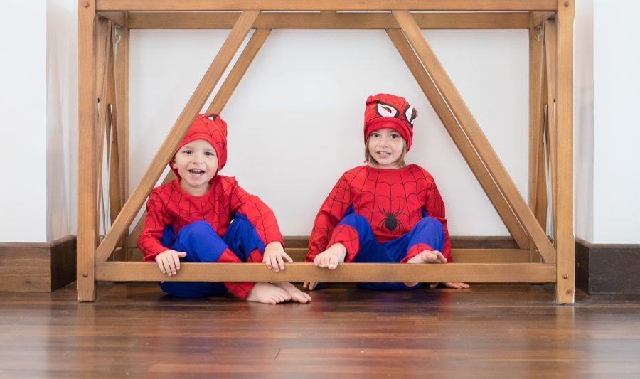 One boy and one girl play dressed as spider man