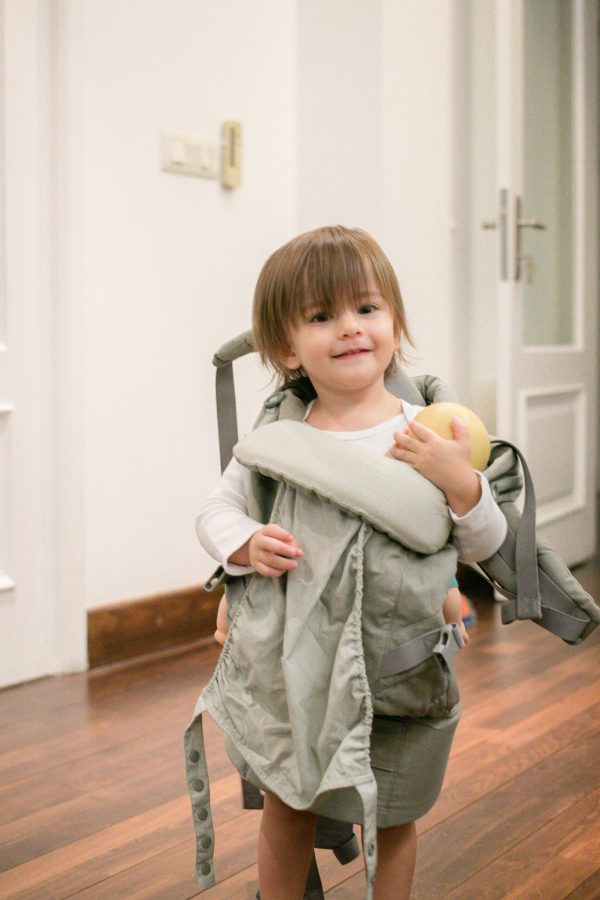 Toddler dresses up like mommy, wearing a baby carrier.