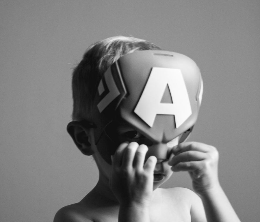 Child wears a superhero mask in his dress up play.